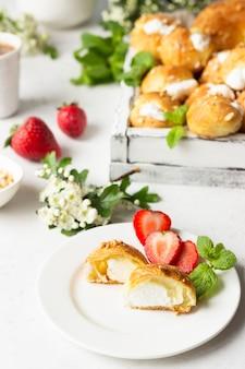 Profiteroles (choux à la crème) - franse choux-deegballen met kwark en room met aardbei, munt en kopje koffie.