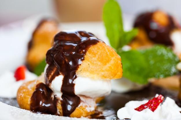 Profiteroles met roomijs en chocolade op plaat