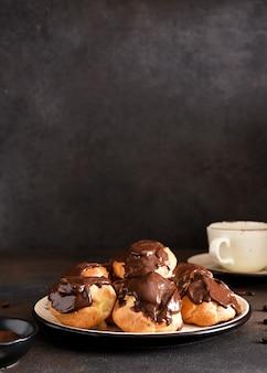 Profiteroles met vanillecrème en chocoladesaus met een kopje koffie op de keukentafel.