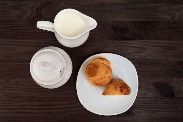 Profiteroles op witte plaat en thee set op houten achtergrond. bovenaanzicht. bakken voor thee.