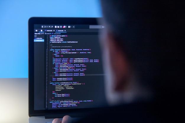 Programmeur die aan laptop computer in bureaustudio werkt