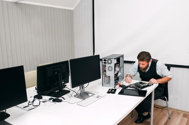 Programmeur die arbeidsmiddelen in open ruimte testen. systeembeheerder inventariseert computers en schermen op kantoor en noteert resultaten in notebook
