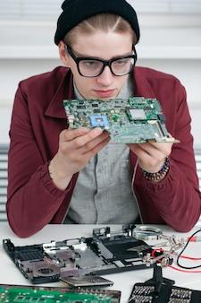 Programmeur die gebroken cpu in workshop bestudeert.