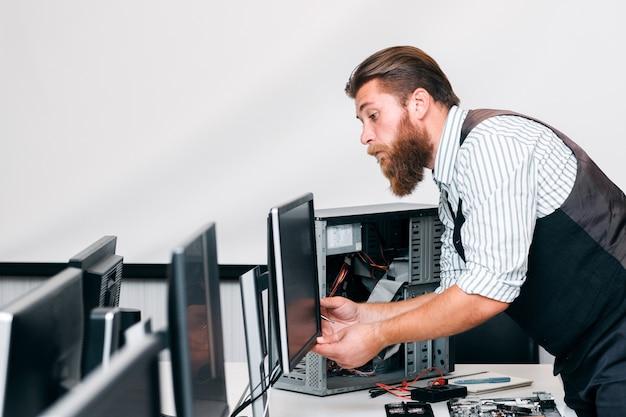 Programmeur die monitor en cpu in bureau verbindt. systeembeheerder die elektronische apparatuur repareert voor bedrijfswerk