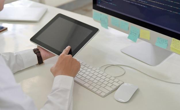 Programmeur mannen met behulp van een tablet in zijn hand met een computerscherm op zijn bureau.