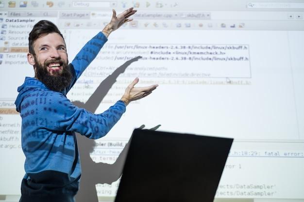 Programmeurcursussen in het onderwijscentrum. de leraar van de man gebaren terwijl hij lesgeeft over technologie
