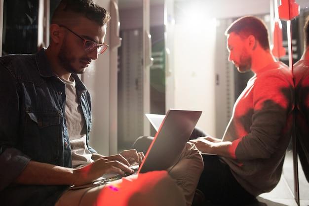 Programmeurs die laptops in serverruimte gebruiken