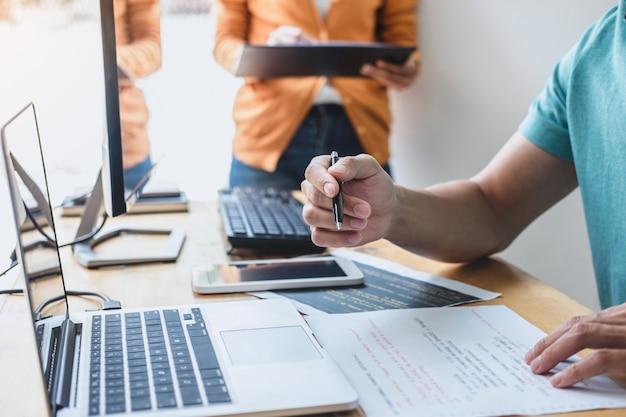 Programmeurs die samenwerken bij developing en website werken in een softwareontwikkelingsbedrijfsbureau