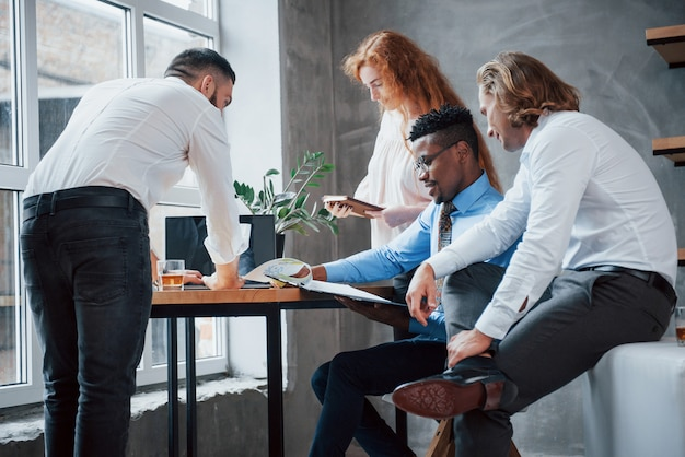 Project bespreken. groep multiraciale kantoormedewerkers in formele kleding praten over taken en plannen