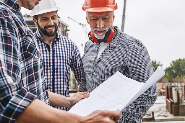 Project bespreken senior ingenieur in formele kleding en helm kijken naar bouwtekening met