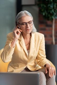 Projectbespreking. mooie grijsharige blanke vrouw met een draadloze headset die deelneemt aan een projectdiscussie die achter een laptop zit