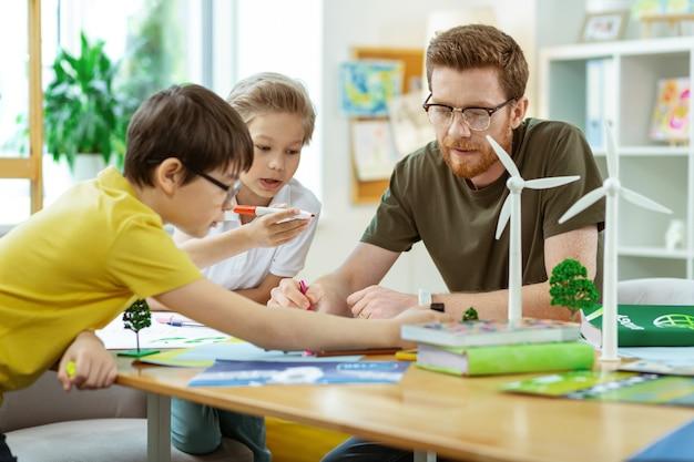 Projectieve affiche. geconcentreerde bebaarde leraar die tijd doorbrengt met zijn nieuwsgierige leerlingen in een uitgerust, helder klaslokaal