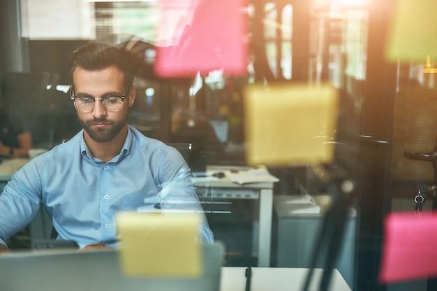 Projectmanagement jonge gefocuste zakenman in bril die aan het werk zit op kantoor aan de voorkant
