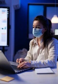 Projectmanager met beschermend gezichtsmasker met professionele laptop voor openbare marketing 's avonds laat in kantoor tijdens wereldwijde pandemie