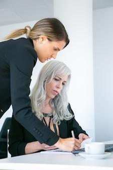 Projectmanager staat in de buurt van werknemer, schrijft notities in document of zet handtekening op papieren rapport. twee vrouwelijke collega's op de werkplek. zakelijke communicatie concept