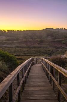 Promenade over de duinen bij zonsopgang met bergen op de achtergrond