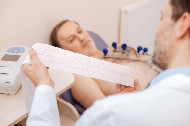 Prominente, nauwkeurige, attente arts die een papieren tape vasthoudt en grafische opnames leest die hij zojuist met zijn patiënt heeft gemaakt