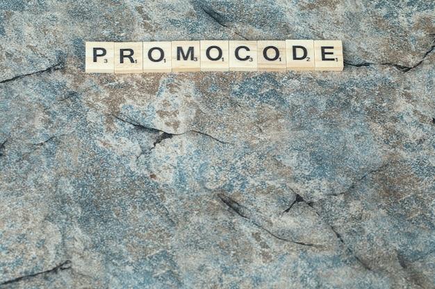 Promocode schrijven met zwarte letters op houten dobbelstenen op het beton