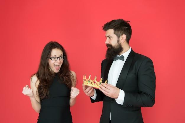 Promotie en beloning. gala koningin. bebaarde man sexy meisje. koninklijk feest. prom paar in formele stijl. prom feest. vakantie vieren. trots en glorie. luxe beloning. succes symbool. feestavond.