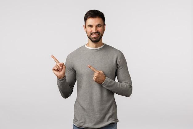Promotie, levensstijl en mensenconcept. knappe blanke man met kralen in grijze trui wijzend in de linkerbovenhoek, met goede promo, advies wat kopen, glimlachend tevreden