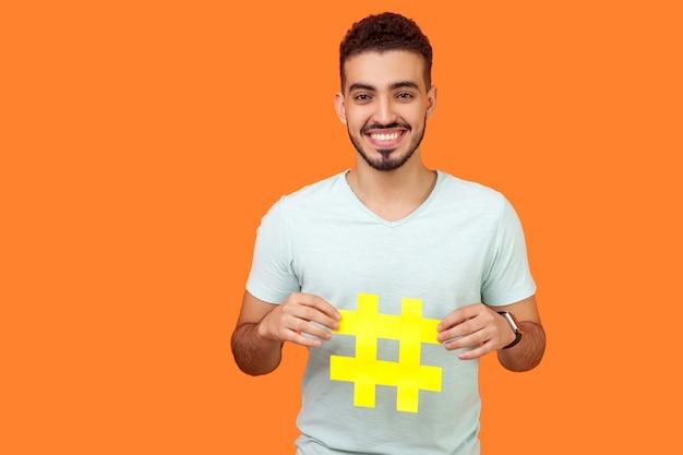 Promotie op sociale media. portret van een gelukkige brunette man met baard in een wit t-shirt die lacht en een groot hashtag-teken vasthoudt en virale inhoud deelt. indoor studio-opname geïsoleerd op oranje achtergrond
