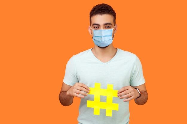 Promotie op sociale media. portret van een gelukkige brunette man met een chirurgisch medisch masker dat lacht en een groot hashtag-teken vasthoudt en virale inhoud deelt. indoor studio-opname geïsoleerd op oranje achtergrond
