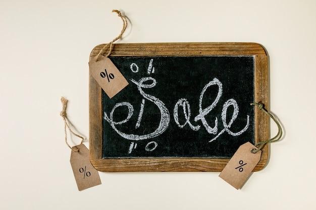 Promotie verkoop concept. vintage bord met handgeschreven krijt belettering verkoop, etiketten met procenten over beige oppervlak. plat leggen.