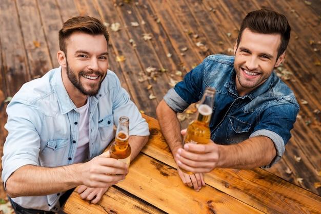 Proost! bovenaanzicht van twee vrolijke jonge mannen die flessen met bier uitrekken en naar de camera kijken terwijl ze buiten staan