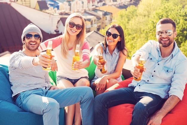 Proost! bovenaanzicht van vier vrolijke jonge mensen die flessen bier vasthouden en met je juichen terwijl ze aan de zitzakken op het dak van het gebouw zitten