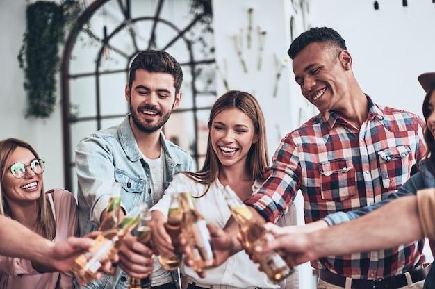 Proost! groep jongeren in vrijetijdskleding die elkaar roosteren en glimlachen