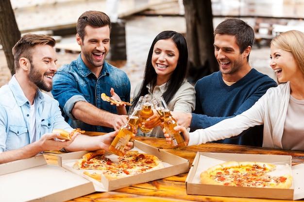 Proost! groep vrolijke jonge mensen die pizza eten en juichen met bier terwijl ze buiten staan