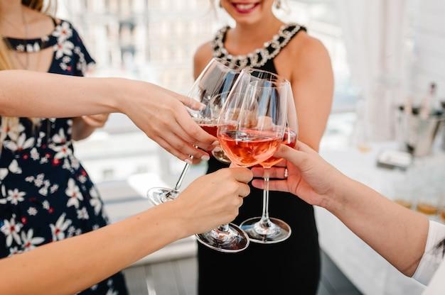 Proost! mensen vieren en heffen glazen wijn op voor toast