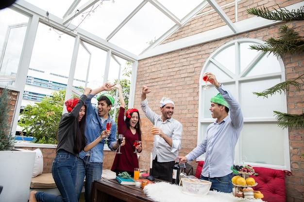 Proost op beste vrienden, vrolijke jonge mensen die juichen met champagnefluiten en er gelukkig uitzien