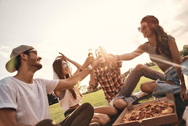 Proost op vrienden! groep jonge lachende mensen in vrijetijdskleding roosteren met bierflesjes terwijl ze genieten van een picknick buitenshuis