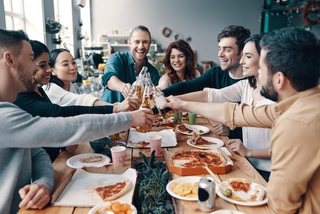 Proost op vrienden! groep jongeren in vrijetijdskleding die elkaar roosteren en glimlachen terwijl ze binnen een etentje hebben