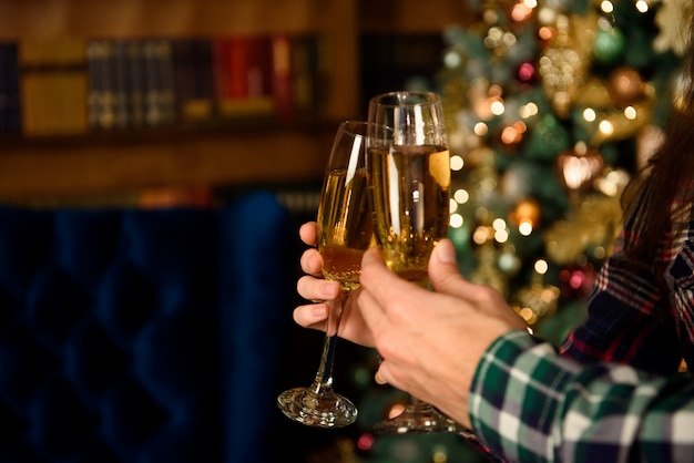 Proost. sluit omhoog foto van twee mensen die glazen shampagne op kerstmis houden.