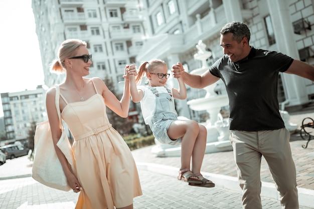 Prop en blijf. klein lachend meisje dat haar vrolijke ouders hand in hand houdt en aan hen hangt terwijl ze op straat lopen.