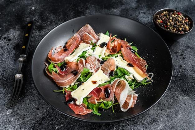 Prosciutto crudo ham salade met brie camembert kaas en rucola op een bord. bovenaanzicht.