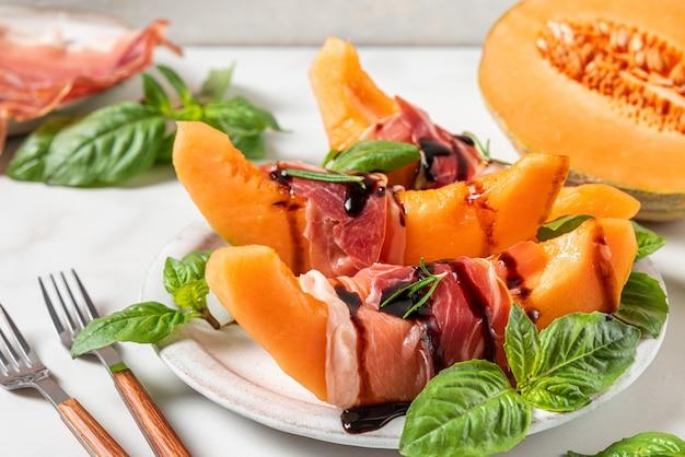 Prosciutto ham met meloen meloen plakjes, balsamico azijn saus en basilicum in een bord met vorken op witte achtergrond. italiaans voorgerecht. detailopname. gezond eten