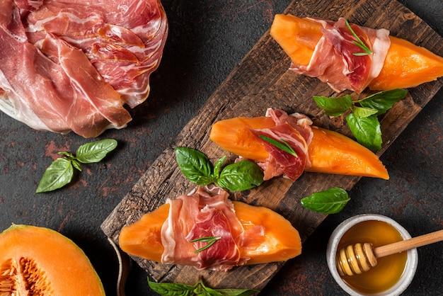 Prosciutto ham met meloen meloen plakjes, honing en basilicum op snijplank over donkere achtergrond. italiaans voorgerecht. bovenaanzicht. gezond eten