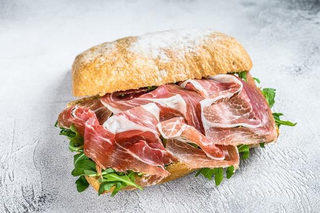 Prosciutto parmaham sandwich op ciabattabrood met rucola. witte achtergrond. bovenaanzicht.