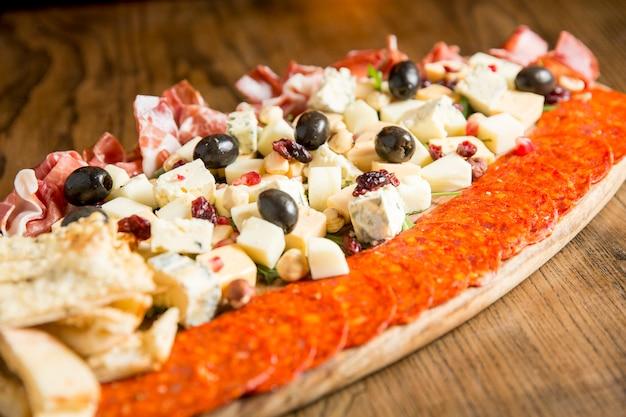 Prosciutto, pittige italiaanse worst en kaas met noten en gekonfijte vruchten