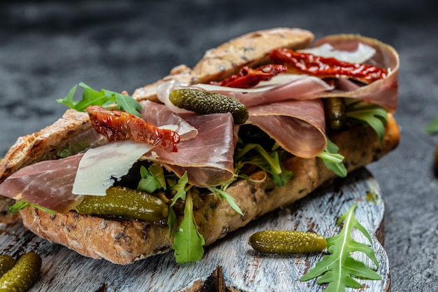 Prosciutto sandwich, ciabatta met prosciutto, zongedroogde tomaten, augurken, parmezaanse kaas en rucola, voedsel recept achtergrond. detailopname