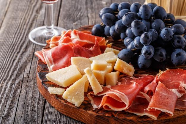 Prosciutto, wijn, druif, parmezaanse kaas op houten tafel.