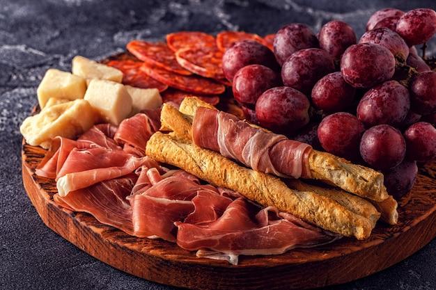Prosciutto, worst, wijn, druif, parmezaan op donkere tafel