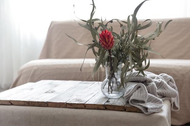 Protea bloem in een glazen vaas en een gebreid element op de tafel in de kamer.