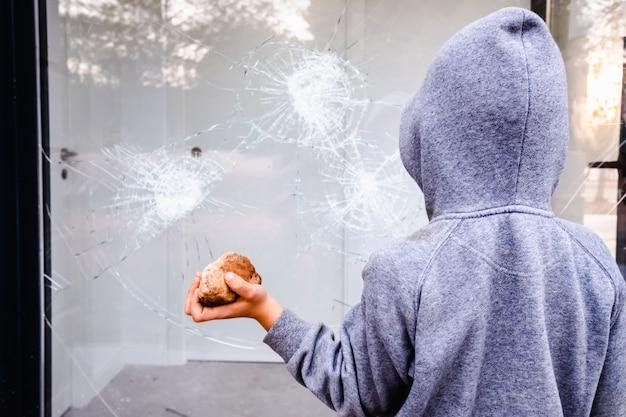 Protesteerder die een rots houden om het glas van een winkelvenster in de straat tijdens protesten te breken.