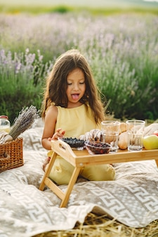 Provence kind ontspannen in lavendel veld. klein meisje in een picknick.