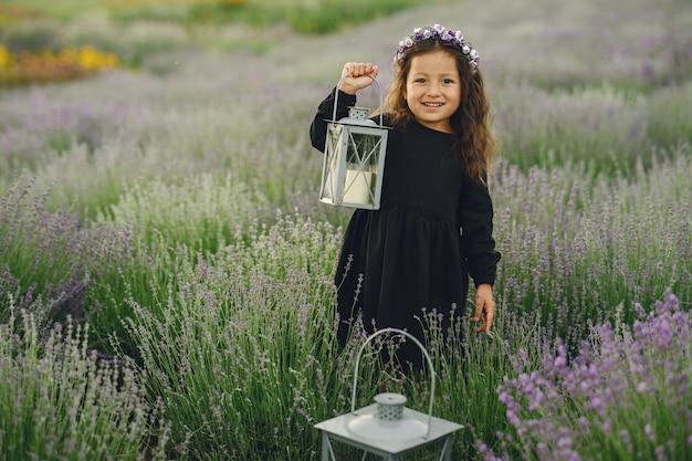 Provence kind ontspannen in lavendel veld. kleine dame in een zwarte jurk. meisje met tas.