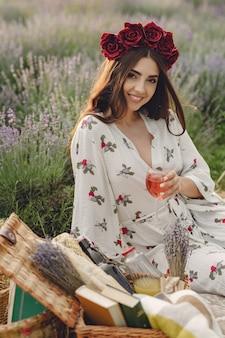 Provence vrouw ontspannen in lavendel veld. dame in een picknick. vrouw in een krans van bloemen.